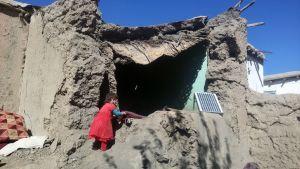 Lapsi seisoo kotinsa raunioilla Afganistanissa.