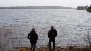 Suomussalmelaiset Oili ja Eero Keränen seisovat kotijärvensä rannalla. Keräset ovat vastustaneet Metsähallituksen hakkuusuunnitelmia Pesiöjärven saarissa. Saaret häämöttävät taustalla.