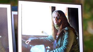 Päihdekuntoutuja Hanne Saarto valokuvassa palaneen talonsa pöydän ääressä.