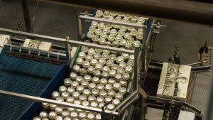 Olvin oluttölkkejä pahvipakkauslinjastolla yhtiön Iisalmen tehtaalla.