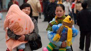 Äitejä kantamassa lapsiaan Chengdussa Kiinassa.