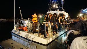 Merestä pelastettuja turvapaikanhakijoita kuljettava alus saapuu satamaan.