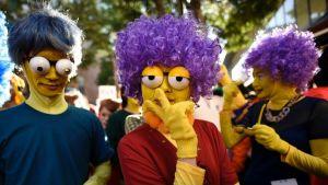 Kolmella halloweenin juhlijalla on keltaiseksi maalatut kasvot, violetit pörröperuukit ja tekomulkosilmät.