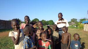 Sudanilaisia lapsia kylän raitilla, taustalla myös opetrtaja.