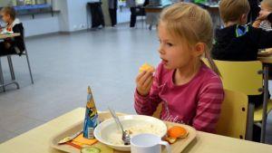 Neela Hukkanen syö appelsiinia Siilinjärven Toivalan koulun ruokalassa. Tarjottimella on jäätelötuutti.