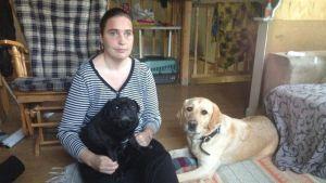 Katja Heinonen, hänellä sylissään musta koira. Vaaleanruskea koira makoilee vieressä.