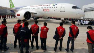 Tuhannet kutsuvieraat seuraavat, kun Kiina esittelee ensimmäisen kotimaassa valmistetun matkustajalentokoneen Shanghain lentokentällä.