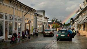 Vanhan Rauman kadulla autoja ja ihmisiä. Taivaalla sadepilviä ja sateenkaari.