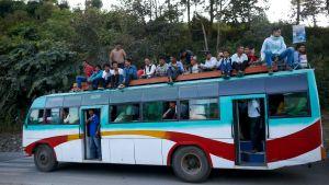 Nepalilainen bussi, jossa ihmisiä istuu myös katolla.