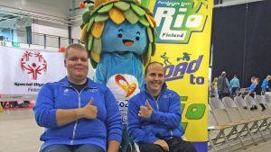 Jousiampuja Jere Forsberg ja ratakelaaja Toni Piispanen näyttävät peukkua Rion paralympialaisten maskotin edessä.
