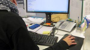 Henkilö työpöydän ja tietokoneen ääressä.