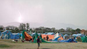 Maanjäristyksestä selvinneitä nepalilaisia suojautumassa ukkosmyrskyltä.