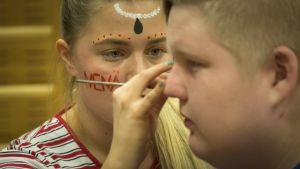 Nenäpäivän riehaa Kiviniityn lukiossa Kokkolassa, kasvomaalaus käynnissä.
