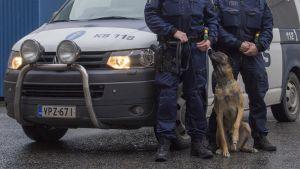 Poliisikoira ja -auto sekä kaksi poliisia.