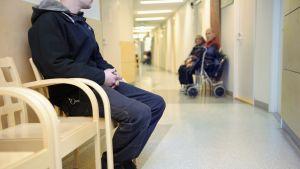Mies odottaa vuoroaan terveysaseman käytävällä Helsingissä 26. marraskuuta.