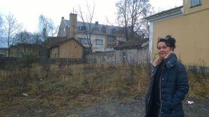 Tiina Jalma palaneen talon tontilla, taustalla näkyy rakennuksia.