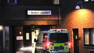 Ambulanssi ensiapuaseman oven edessä.