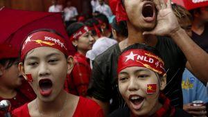 Kolme NLD-puolueen punaisiin päänauhoihin sonnustautunutta nuorta huutaa suureen ääneen.