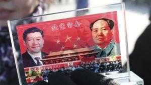 Muoviteline, johon on upotettu Xin ja Maon sekä marssivan armeijan kuvat.