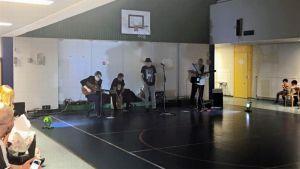 Bändi soittaa jumppasalin perällä