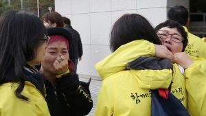 Neljö naista itkee ja halaa oikeustalon edustalla.