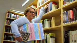 Naisella on kirjoja kainalossa ja hän haluaa hyllystä lisää