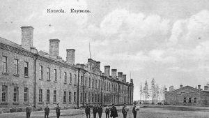 Kuvassa näkyy Kouvolan kasarmin tiilirakennus ja paraatikenttä,jossa seisoo sotilaita venäläisissä univormuissa.