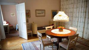 Näkymä asuntoon. Etualalla pöytä ja tuoleja. Taustalla sänky ja ovi toiseen huoneeseen.