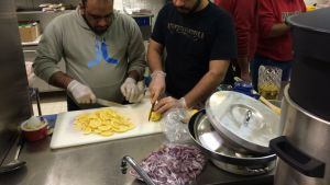 Miehet laittavat ruokaa laitoskeittiössä