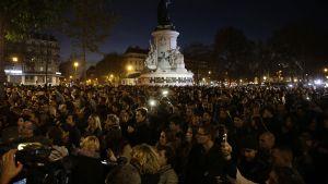 Ihmisiä kerääntyneinä muistamaan terrori-iskujen uhreja Place de la Republique -aukiolle Pariisissa.