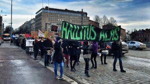 """Useita kymmeniä mielenosoittajia marssii Tampereen Hämeensillalla. Suurimassa banderollissa lukee """"hallitus alas""""."""