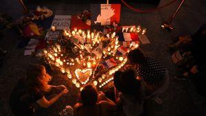 Sydämen muotoon asteltuja kynttilöitä ja ihmisiä maassa niiden ympärillä.