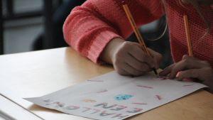 Tyttö piirtää koulussa