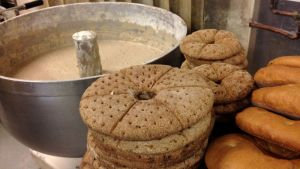 Ruis- ja vaaleita leipiä taikinatonkan vieressä.