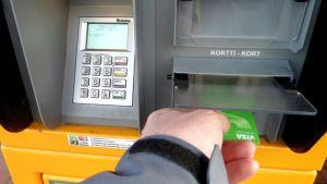 Mies laittaa pankkikorttia tankkausautomaattiin