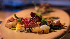 Salaatti perunoista, kinkusta ja kananmunasta tarjoiluvadilla.   Salaatissa on monenlaista suolaisessa ympäristössä kasvavaa: jääpäivikkiä, suolayrttiä ja perunaa.