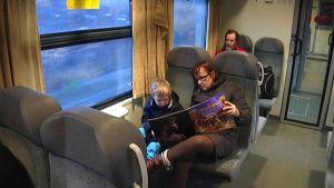 Nainen lukee pojalle junanvaunussa.