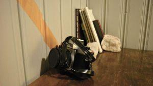 Kamera ja kirjoja pöydällä.