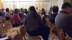Kuvassa istuu ihmisiä tuoleilla koulun liikuntasalossa. Edessä pitkätukkainen nainen puhuu mikrofoniin. Takana näkyvät puolapuut.