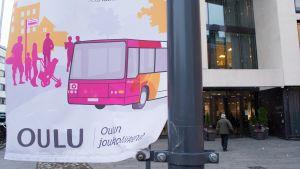 Oulunjoukkoliikenteen lippu Oulu10:n edessä.