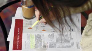 Nainen tutkii maahanmuuttoviraston infopakettia liittyen turvapaikan hakemiseen Suomesta.