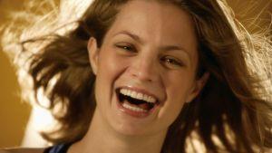 Nuori nainen katsoo kameraan ja nauraa niin, että hampaat näkyvät.