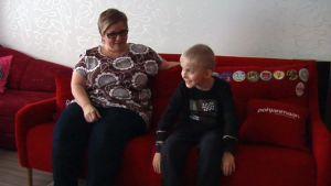 Nainen ja poika istuvat sohvalla
