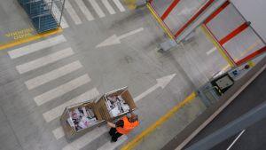 Postin työntekijä kuljettaa lähetyksiä häkeissä