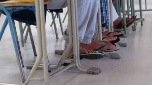 Varvastossuisia miesten jalkoja pulpettien alla