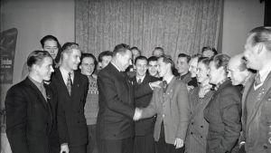 Harald Roos onnittelee Karhu-Kissoja edustavaa jääkiekkoilija Unto Viitalaa Hotelli Helsingissä Suomen jääkiekkojoukkueen saapuessa ottelumatkalta Tsekkoslovakiasta 5. tammikuuta 1949.