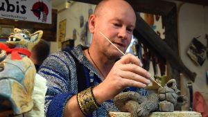 Keramiikkataiteilija työssään muotoilemassa kissaa