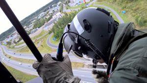Sotilas helikopterissa moottoritien ja teollisuustaajaman yläpuolella