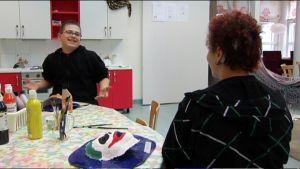 Kaksi lasta keskustelemassa pöydän ääressä.