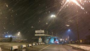 Vaasan satamassa lumipyry ja autoväylä kohti laivaa.